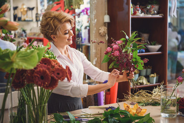 Inspired woman creating bouquet in workshop