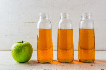 Fresh juice from green Apple in a glass small bottle on a white