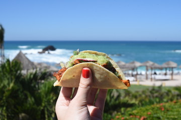 Person holding taco outdoors in summer
