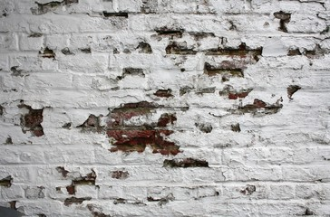 Old brick wall with blathering white paint.