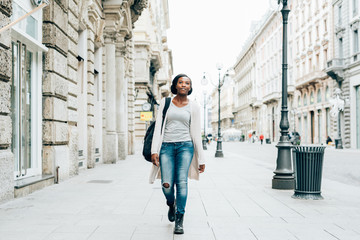Young beautiful black woman outdoor in the city, looking at camera smiling wearing back pack - happiness, carefree, serene concept