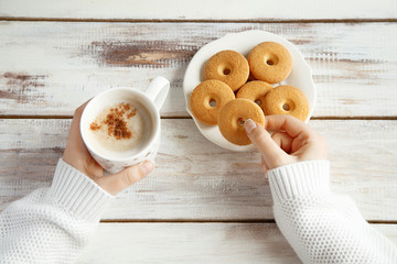 Holding warm coffee and eating cookies on a winter day. Woman hands. Top view