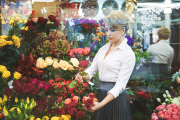 Calm woman making bouquet in shop