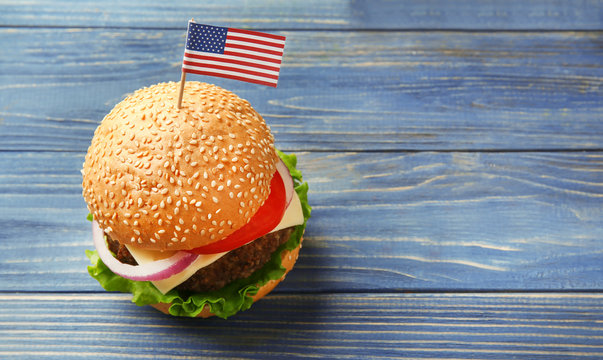 Tasty burger with American flag on wooden table