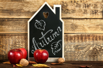 Beautiful autumn composition with chalkboard on wooden background