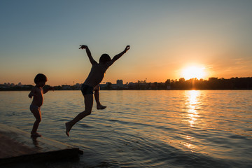 Boy jumping into the water. Sunset. Silhouette frame