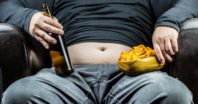 ein Mann sitzt in einem Sessel und ernährt sich ungesund von Bier und Kartoffelchips
