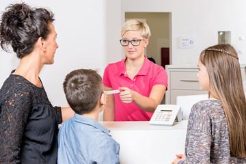 Junge Zahnarzthelferin nimmt Versichertenkarte einer Mutter mit