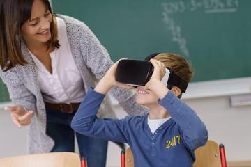 lehrerin und schüler mit einer vr-brille im unterricht in der grundschule