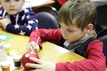 Boy painting Christmas ball