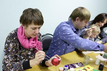 Woman painting Christmas ball