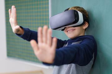 kleiner junge mit virtual reality brille streckt die hände nach vorne