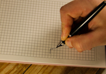 Male hand writing using fountain pen on a notebook