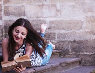 young beautiful girl reading a book outdoors (education, self de