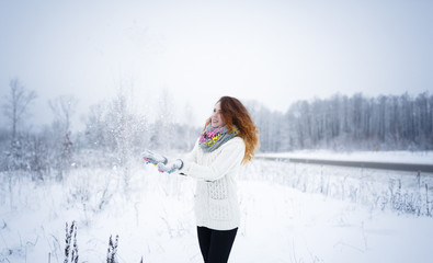 red-haired girl enjoys the winter. a lot of snow. winter. forest. trees. portrait. cloudy weather. throws snow