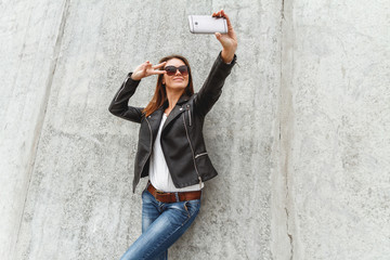 Young beautiful girl in jeans and a black leather jacket makes selfie from the concrete wall