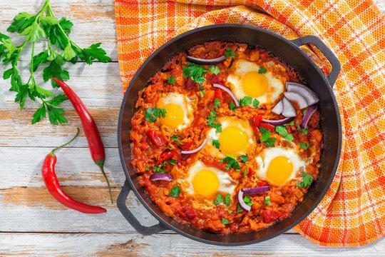 healthy breakfast shakshuka - fried eggs, tomato, pepper and spi