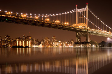 Beautiful night view with lights of Robert F. Kennedy RFK bridge formerly known as the Triborough bridge from Astoria Queens across the East River toward New York City upper Manhattan skyline