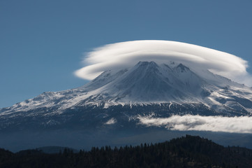 A cloud surrounding the top of a snow capped mountain.