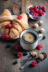 Coffee and croissants with raspberries and fruits for breakfast. Toned image, selective focus