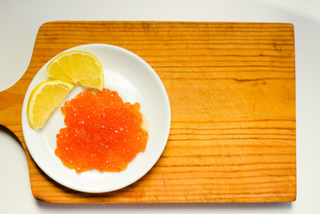 Red caviar, lemon and bread on wooden board white table background
