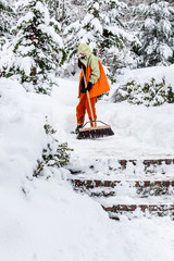Boy uses a push broom to sweep snow off a front path and steps of his house