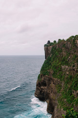 The pictersque rock in the ocean with the temple on te top. Azure waves with white foam of Indian ocean, Indonesia, Bali, Uluwatu