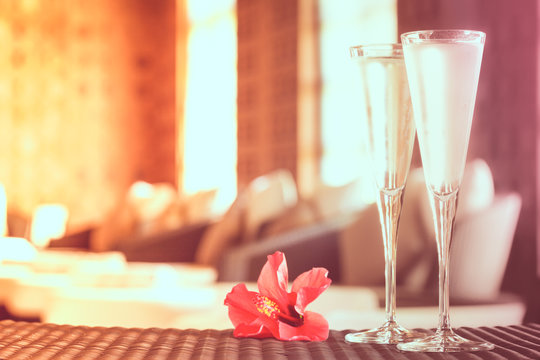 Two glasses of champagne with red flower in a spa lounge. Spa ti
