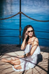 A young woman with sunglasses sitting on a pier in Eilat, Israel.