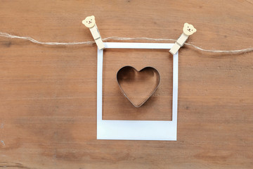 vintage photo frame on rope with clothespins and heart shape on