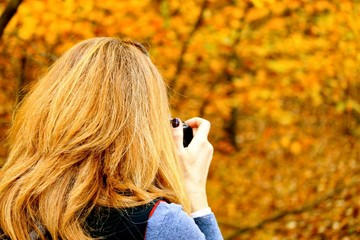 Woman whose hair matches landscape is photographing fall foliage in Indiana Dunes