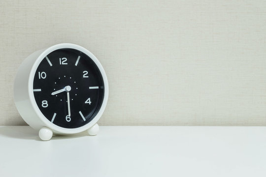 Closeup black and white alarm clock for decorate show show half past eight or 8:30 a.m. on white wood desk and cream wallpaper textured background with copy space