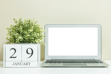 White wooden calendar with black 29 january word with white blank space at center of computer notebook on white wood desk and cream wallpaper textured background , selective focus at the calendar