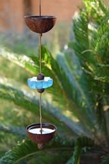 Regenkette aus Glas und Metall vor einem Gartenhintergrund an einem sonnigen Tag