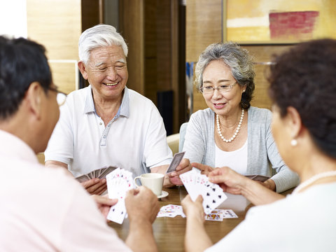 senior asian people playing cards