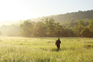 A man is hiking on grass field background early morning, sunny and blue sky