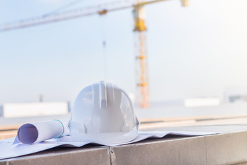 The white safety helmet and the blueprint at construction site w