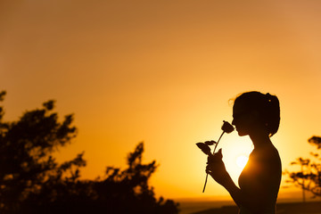 Woman smelling a rose against a beautiful sunset. Romantic gift concept.