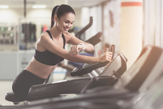 Smiling girl controlling her results in a gym