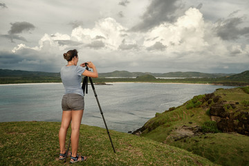 Tourist traveler photographer making pictures on background sea coast and mountains