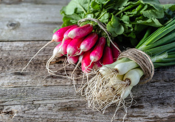 Bunch of radish and onion, green vegetables, local market produce on farm table