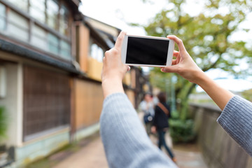 Taking photo by cellphone in old town of Japan