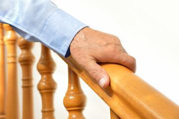 hand of senior man over a wooden railing