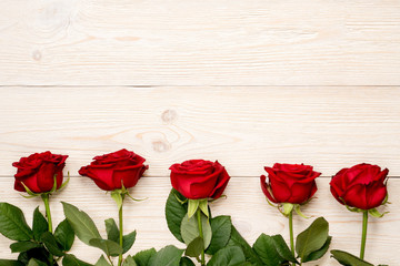 5 red roses in row on white rustic desks