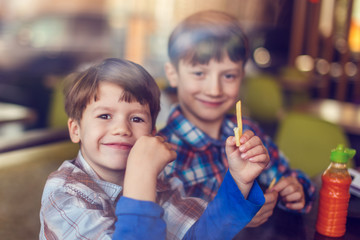 Little boys eating french fries in fast food restaurant