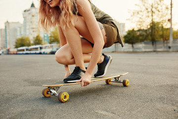 Beautiful young girl with tattoos sits on longboard in sunny weather