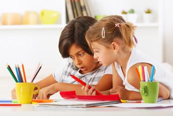 Two girls playing together with pencils and color paper.