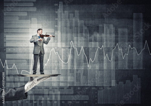 Businessman on metal tray playing violin against graphs and diagrams