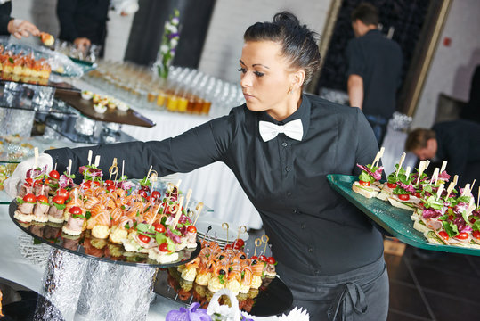 Waitress serving catering table