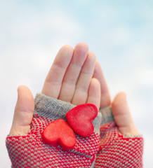 Two red decorative hearts in female hands on a light background. Romantic card by St. Valentine's Day